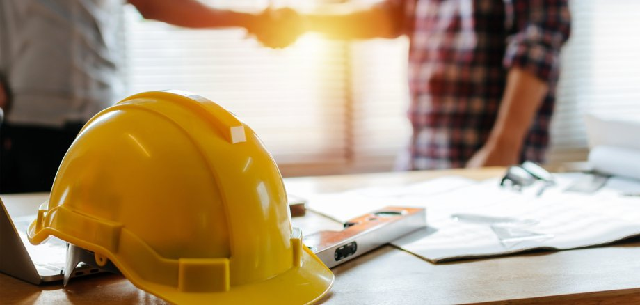 yellow safety helmet on workplace desk with construction worker